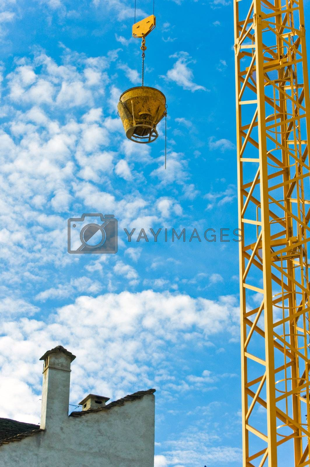 Yellow crane near building standing against blue sky with fluffy clouds.