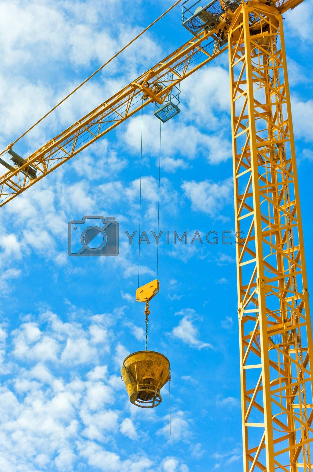 Yellow crane against blue sky with fluffy clouds.