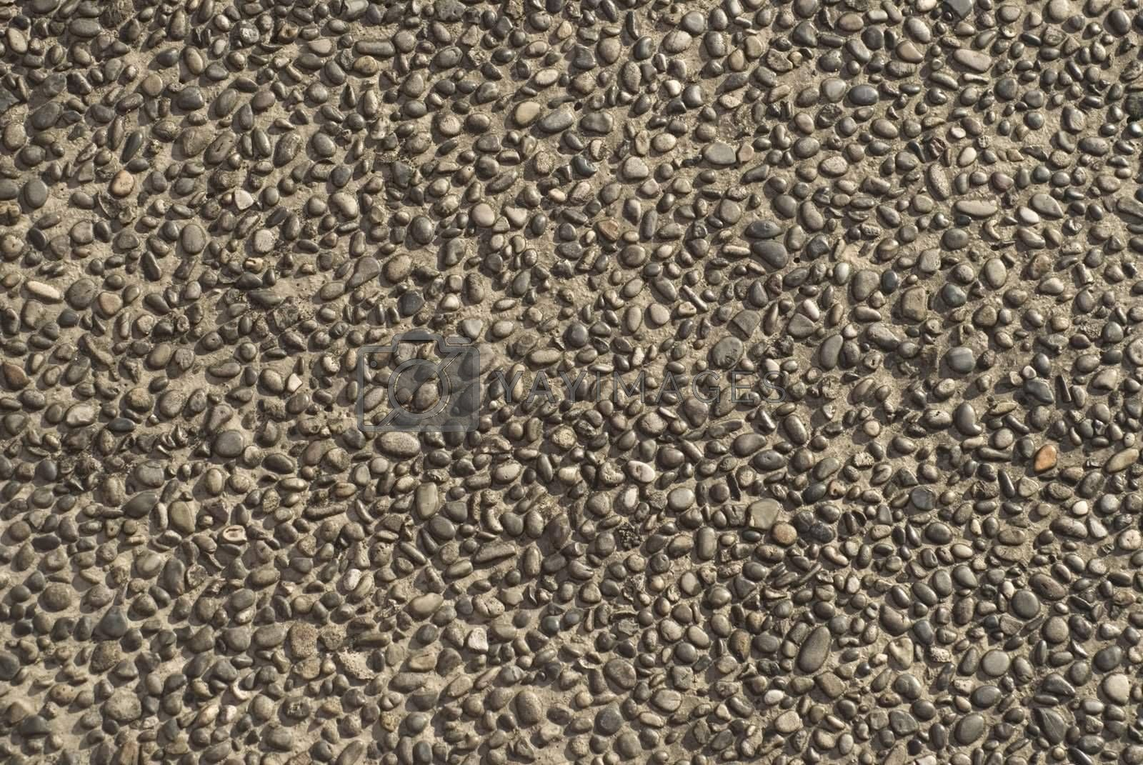 Close up of detail of concrete paving with tiny pebbles in sidewalk.