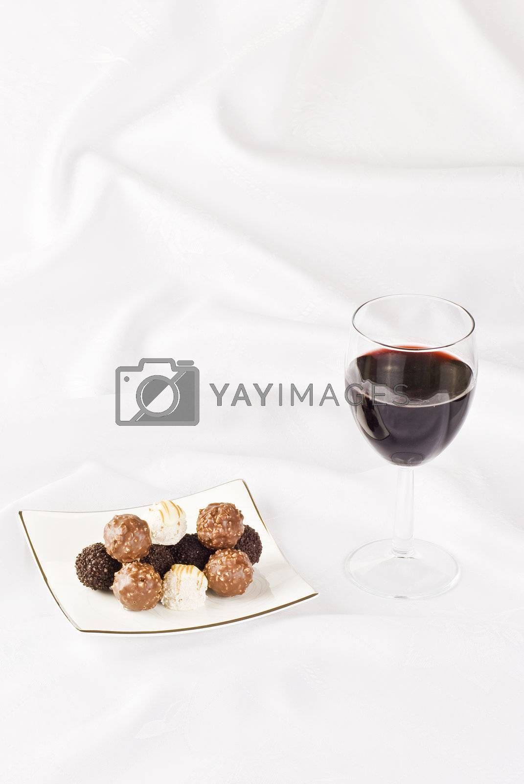 Glass of red wine and chocolate by caldix