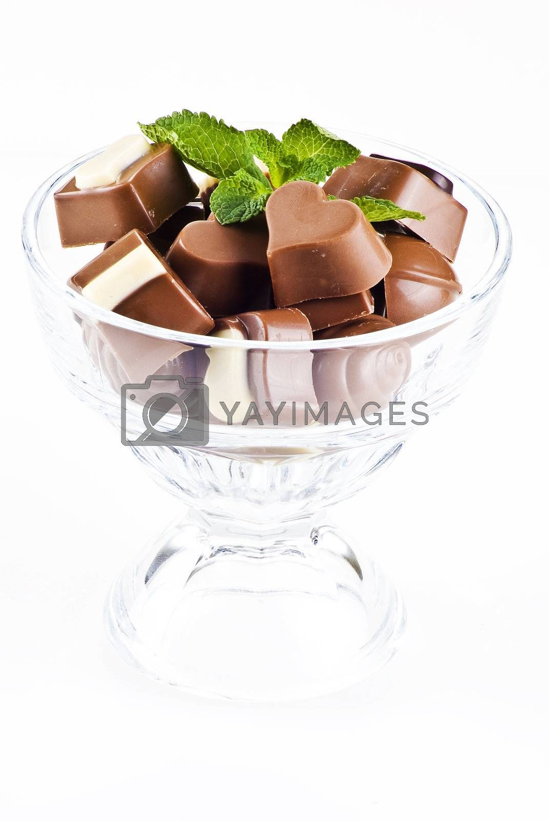 Glass bowl of chocolates and mint by caldix