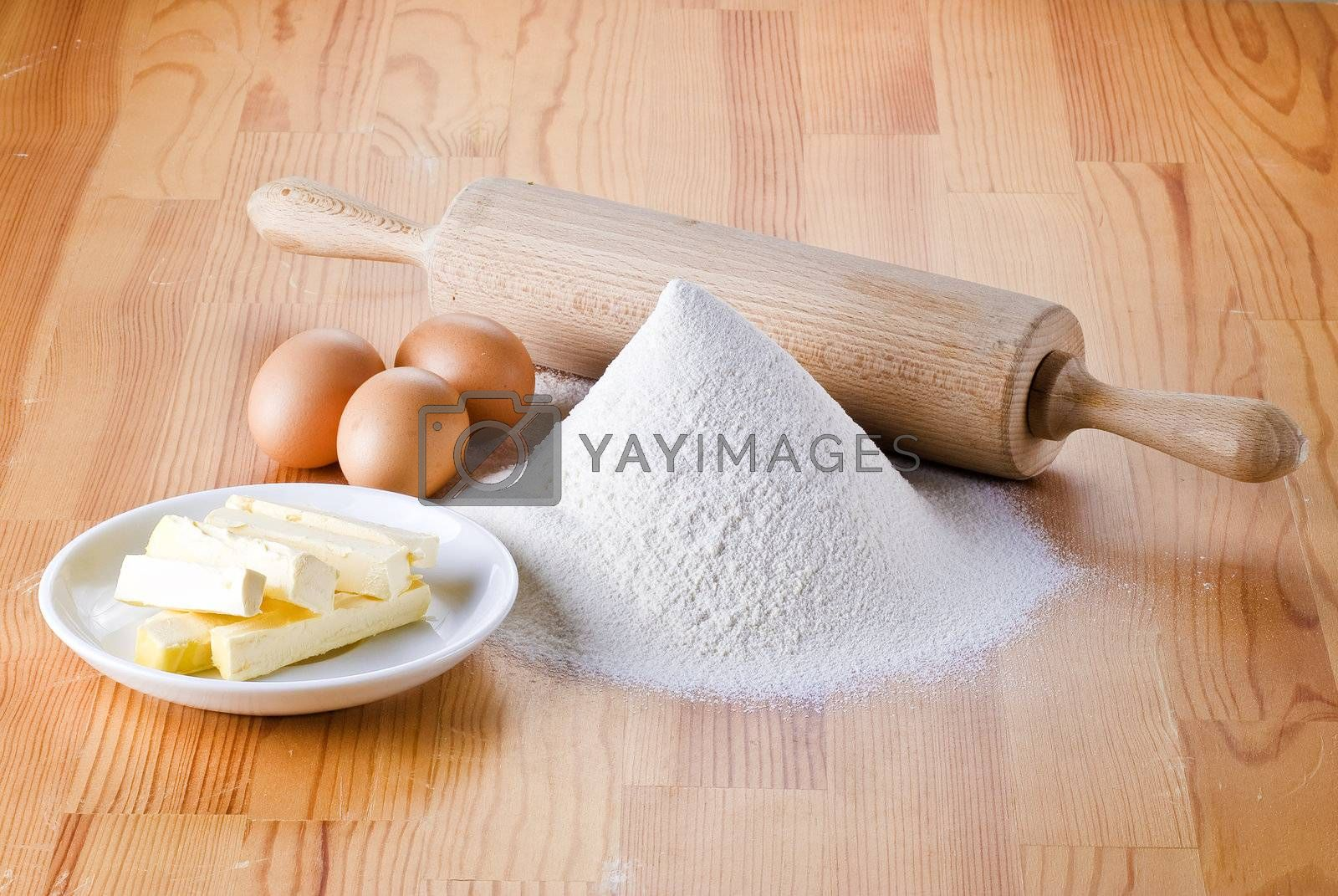 Flour with eggs, rolling pin and butter by caldix
