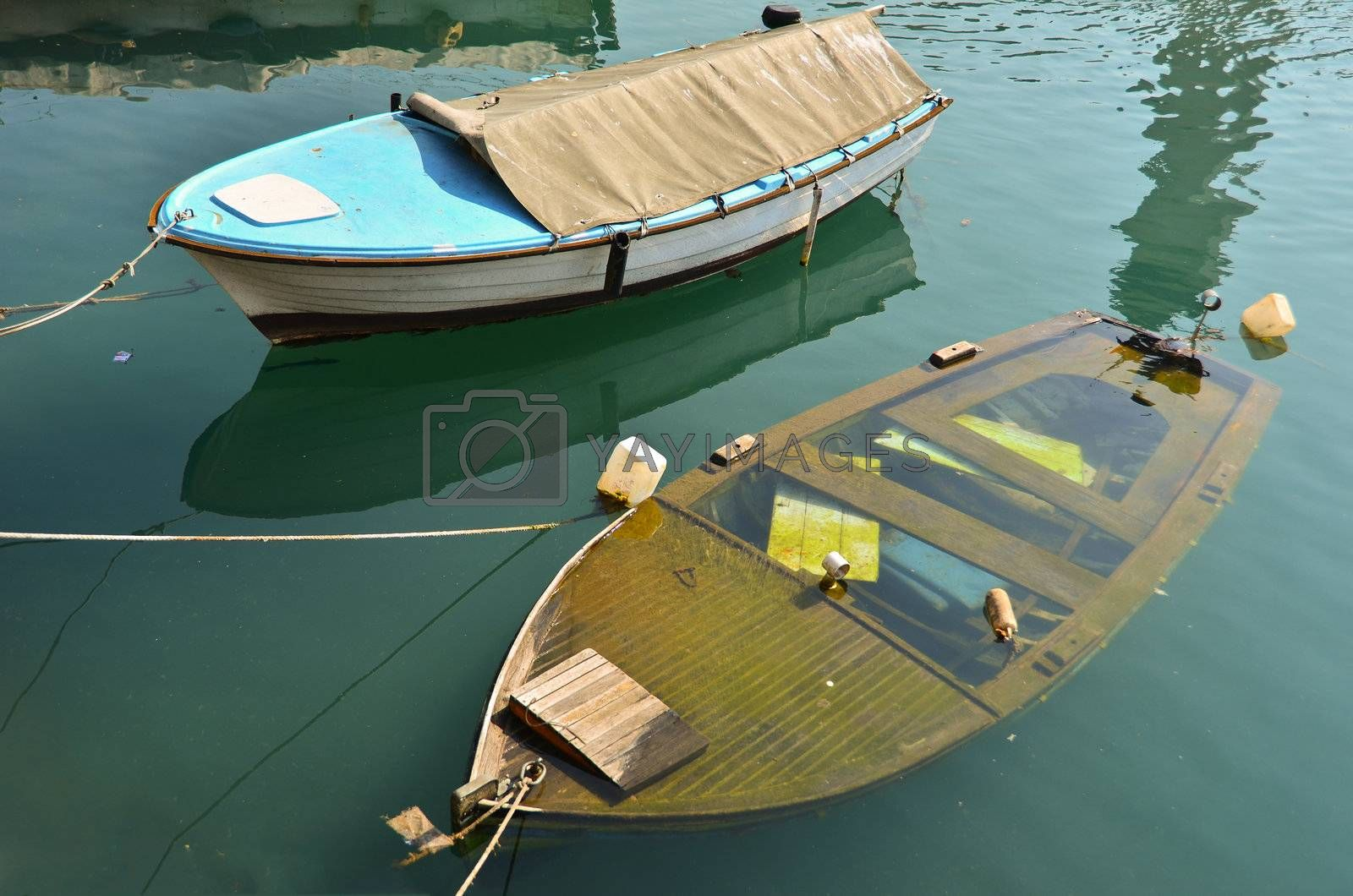 Two boats on berth, plastic blue one, and wooden one is sinking