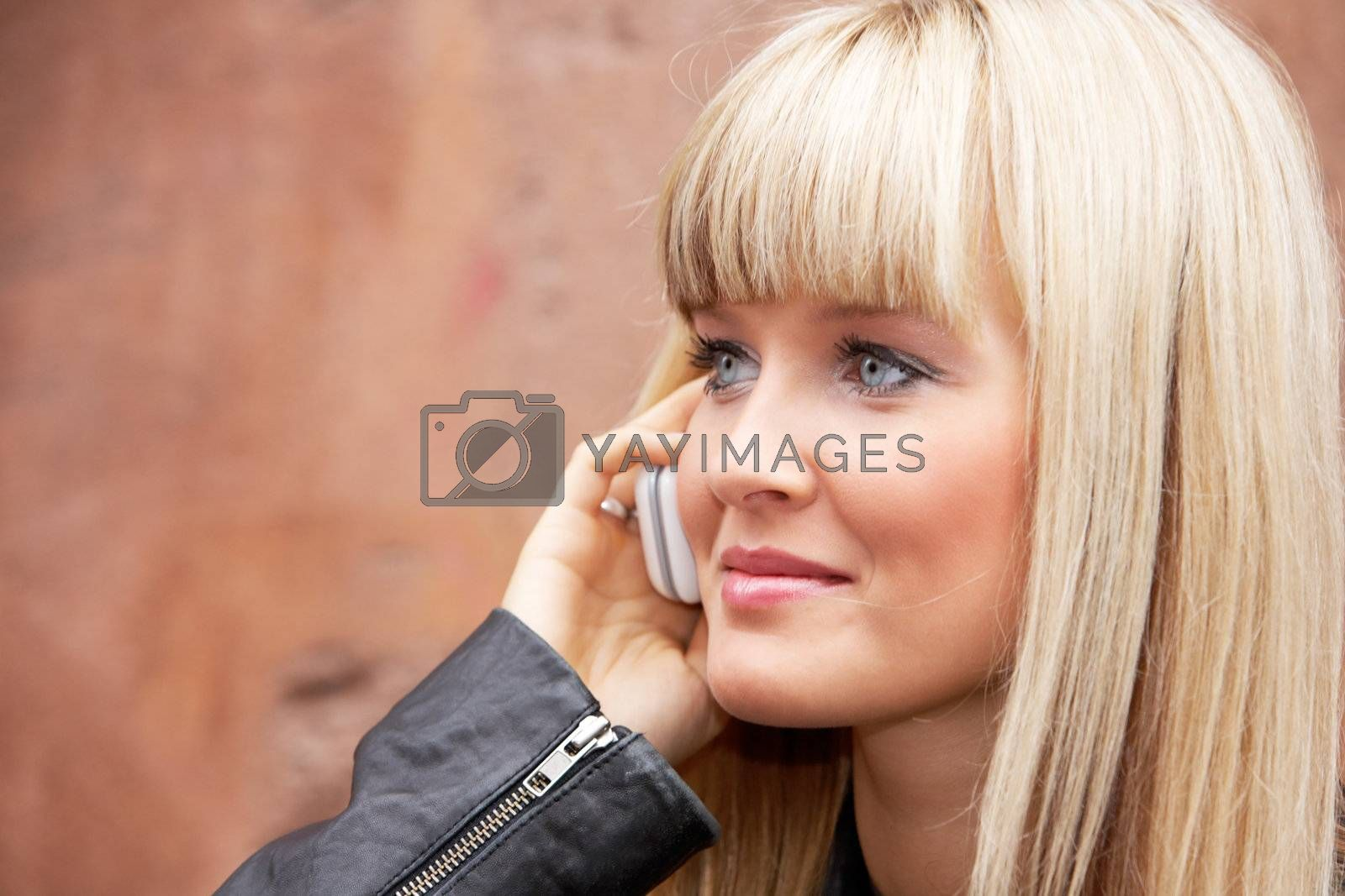 Young woman using mobile phone by building wall