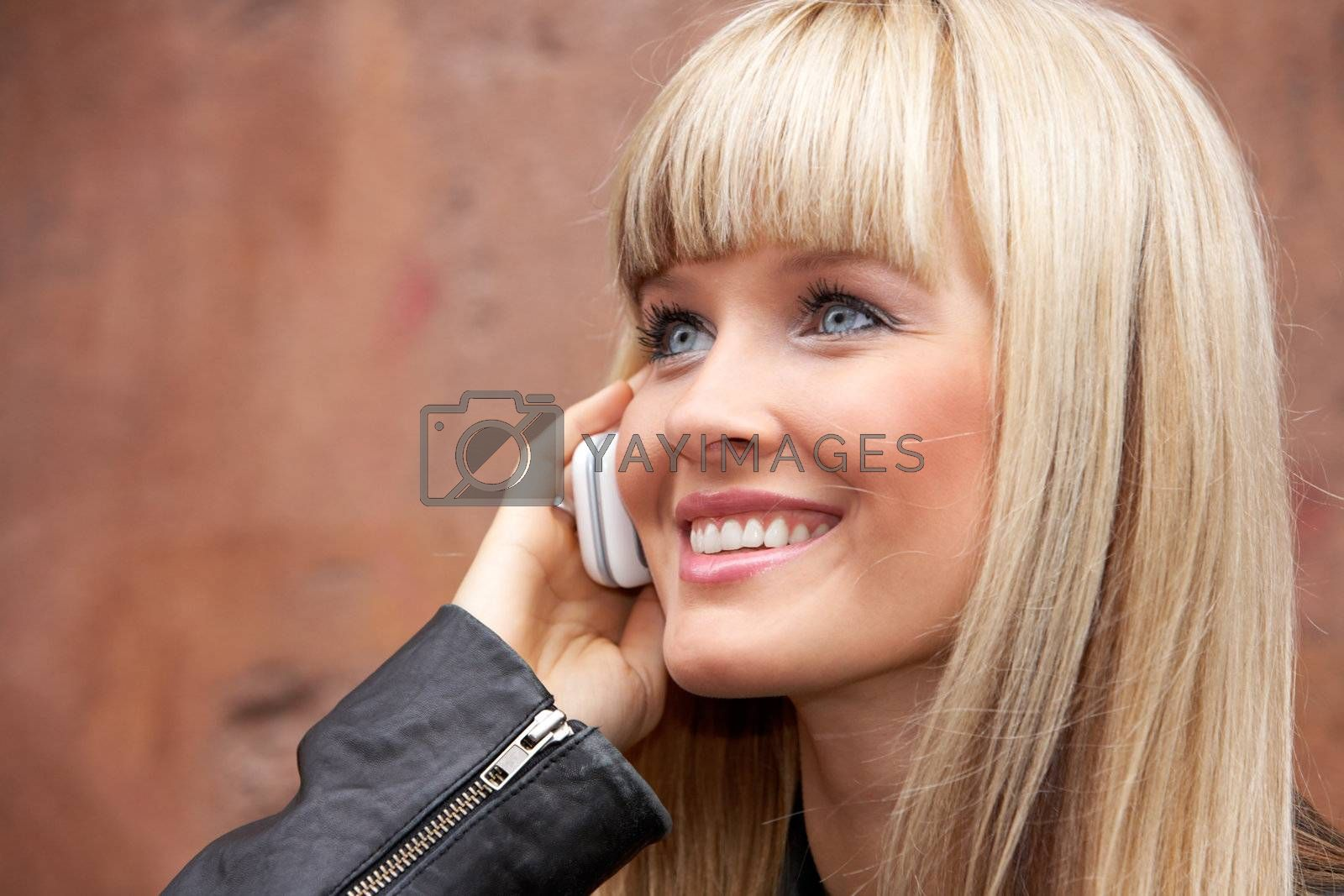 Young woman using mobile phone, smiling