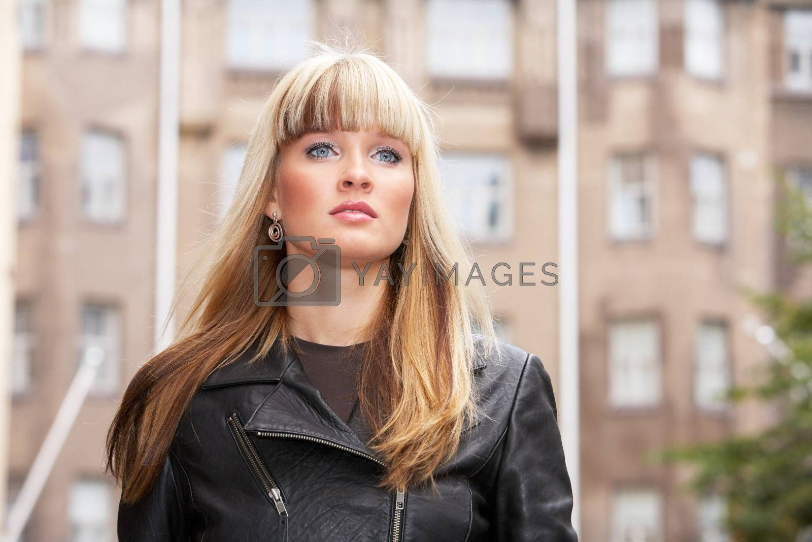 Portrait of young woman standing in city, looking away