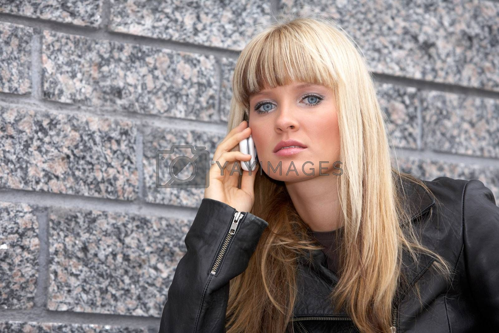 Young woman using mobile phone, looking at camera