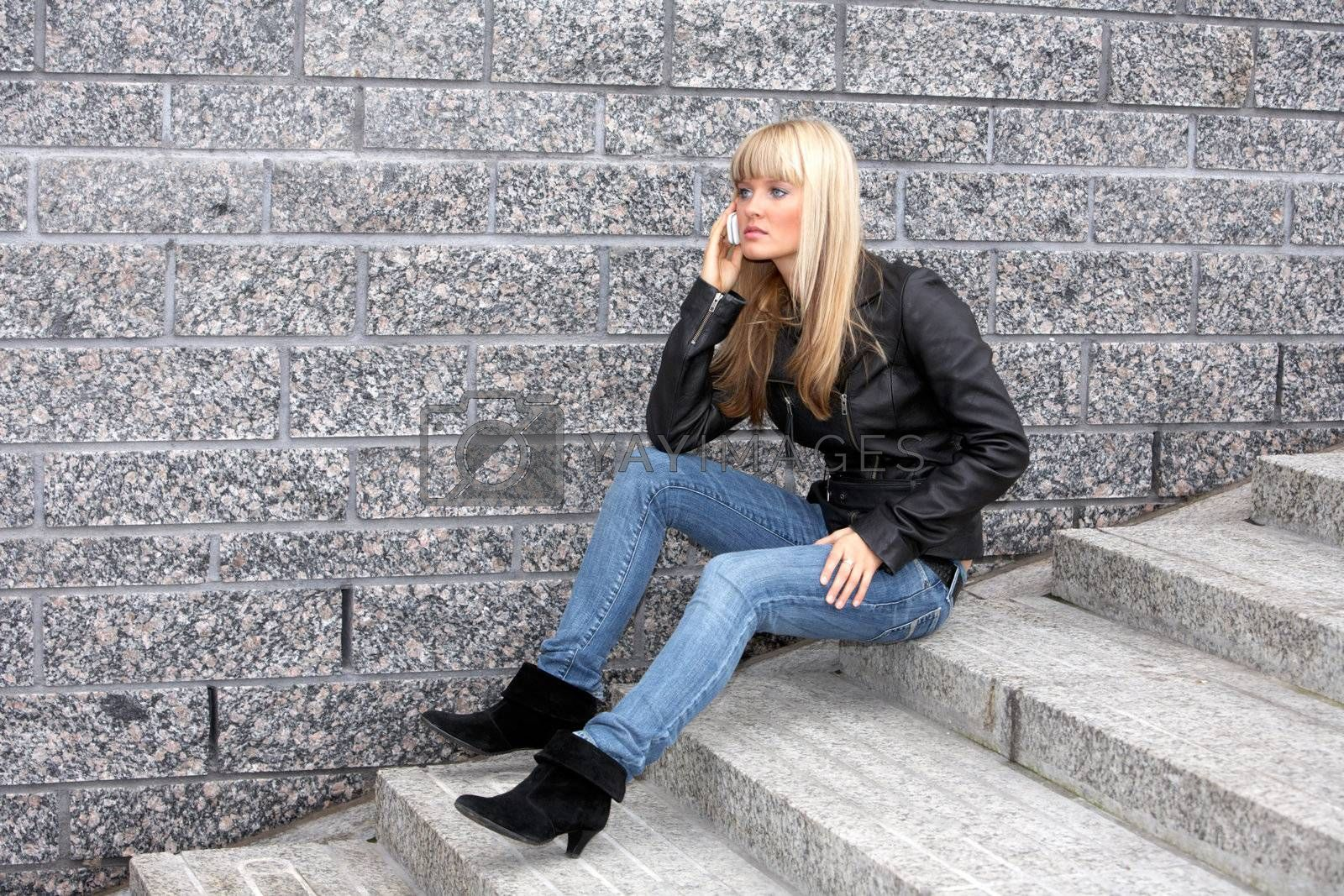 Young woman using mobile phone, sitting on stairway