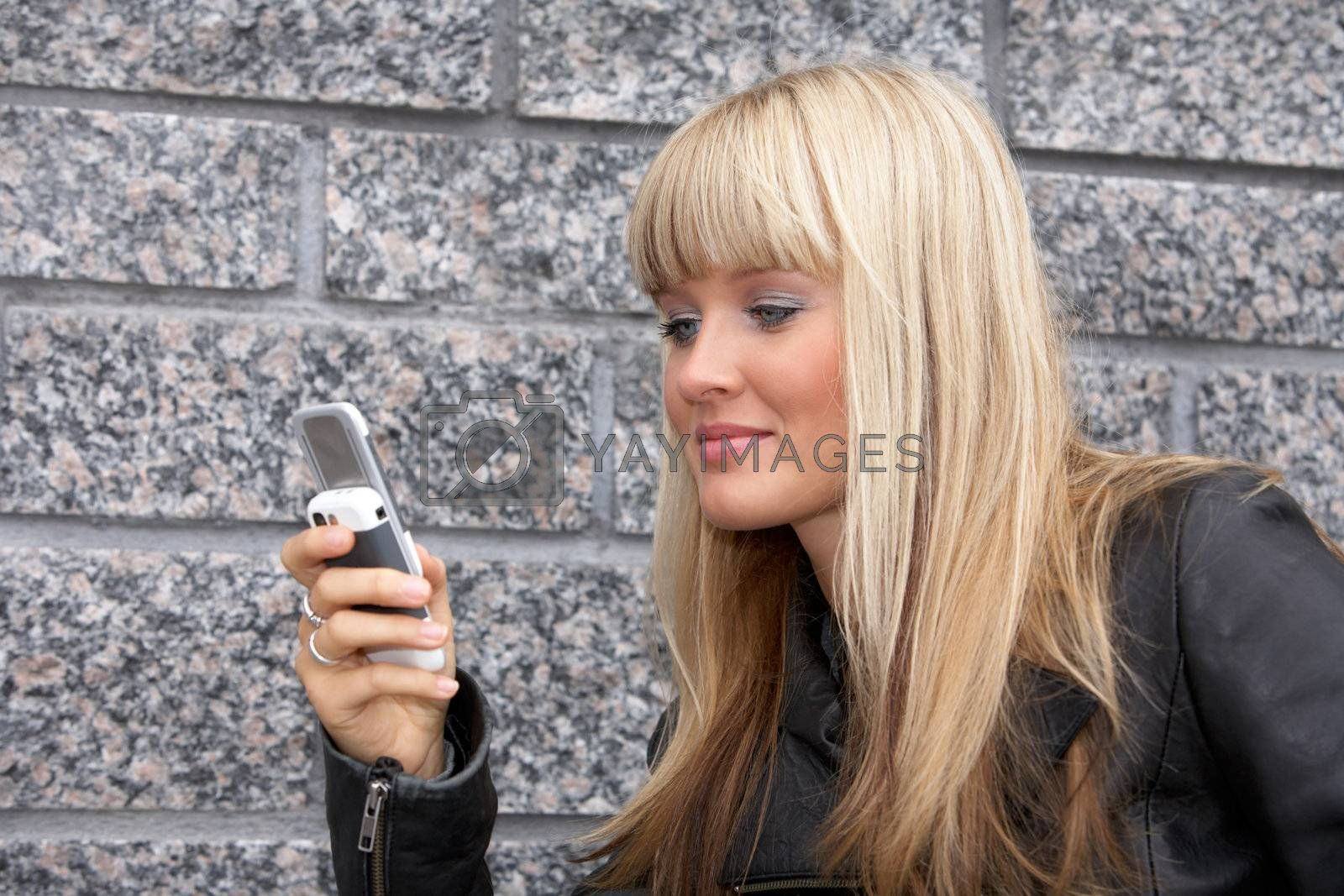 Young woman looking at mobile phone, smiling