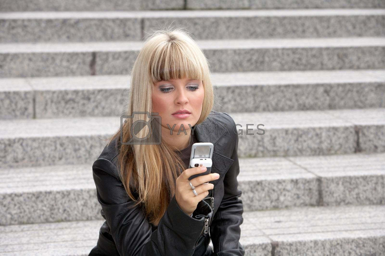 Young woman looking at mobile phone while holding it in hand