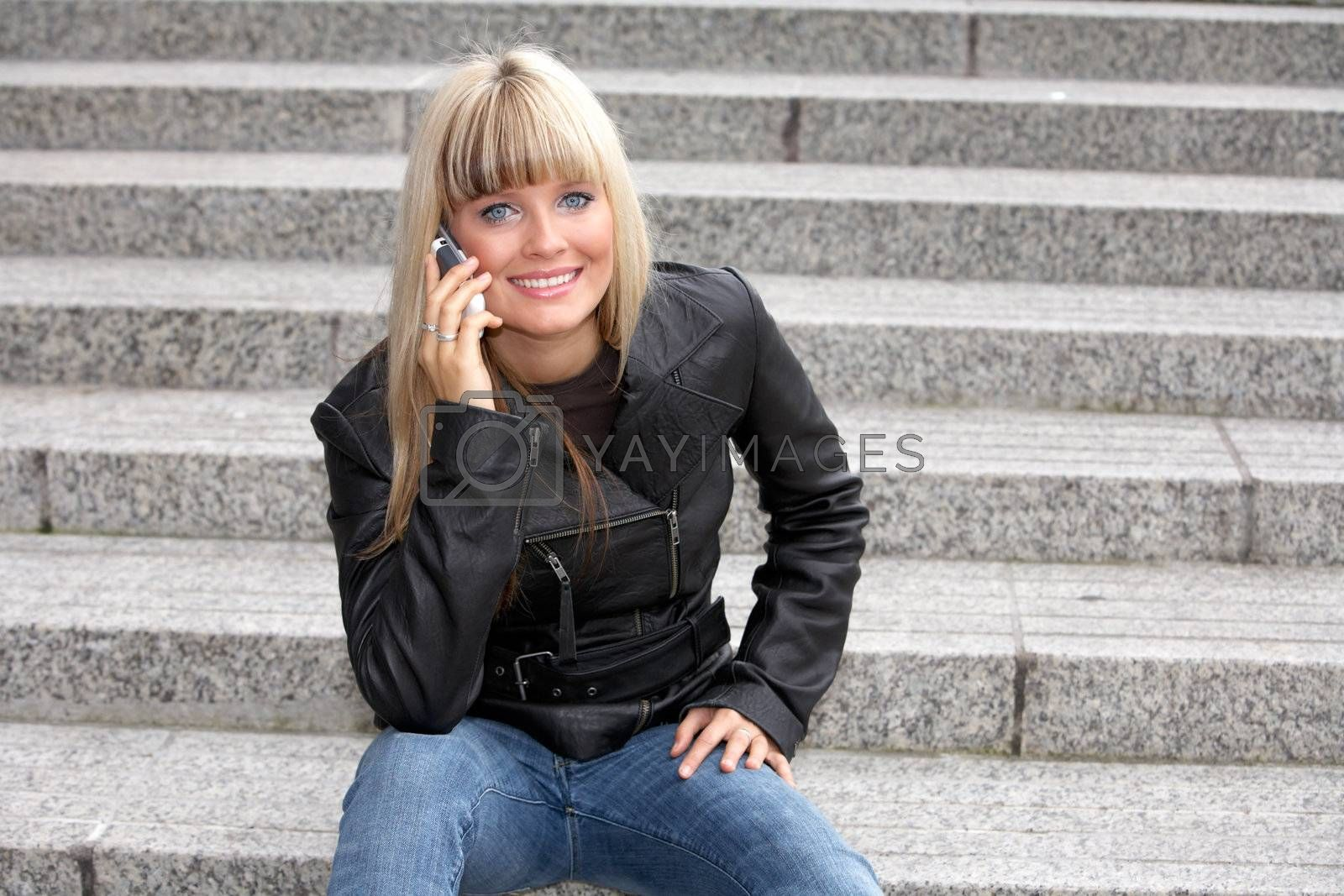 Young woman with mobile phone, looking at camera, smiling
