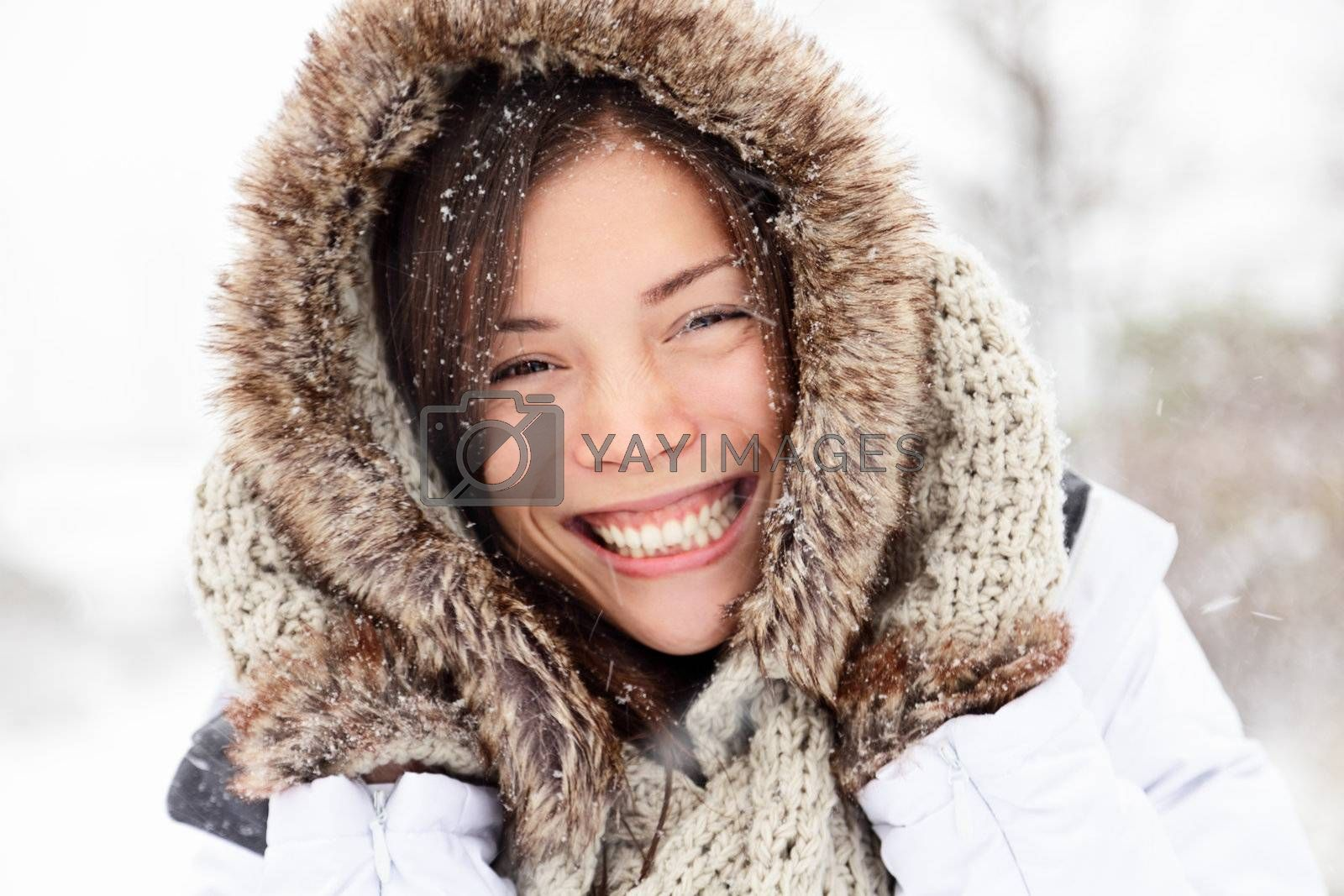 winter woman happy outside in snow smiling joyful on snowing winter day. Cute closeup portrait of beautiful mixed race Caucasian Asian girl cheerful and excited outdoors.