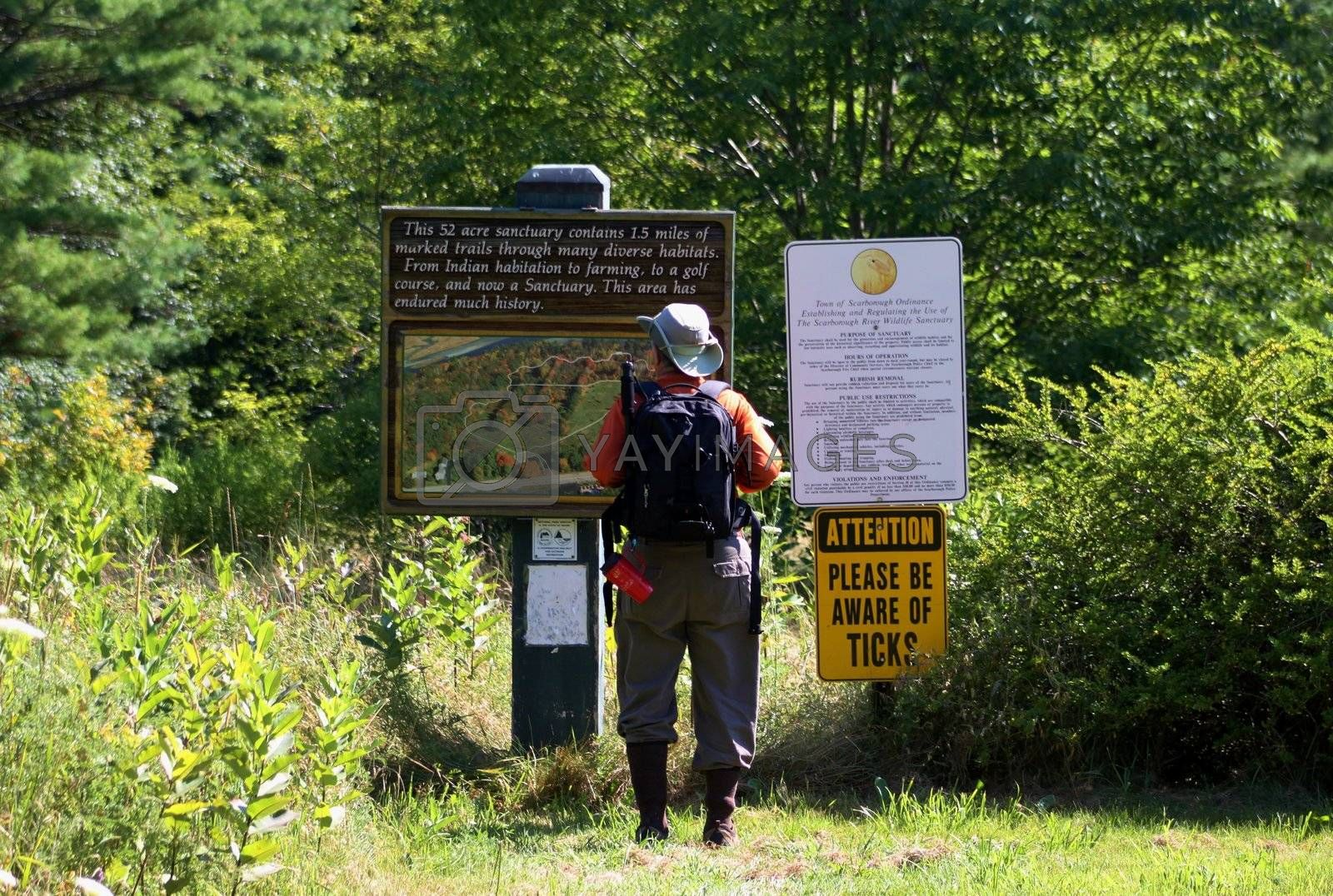 Hiker seeking information from a board on a pathway