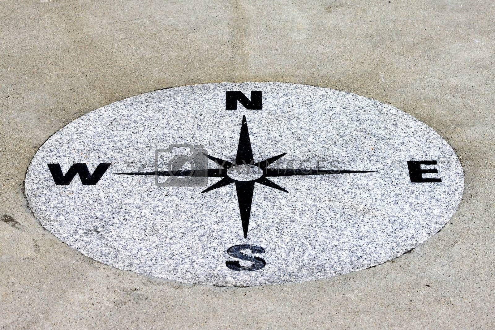 Compass found on a sidewalk on a granit background