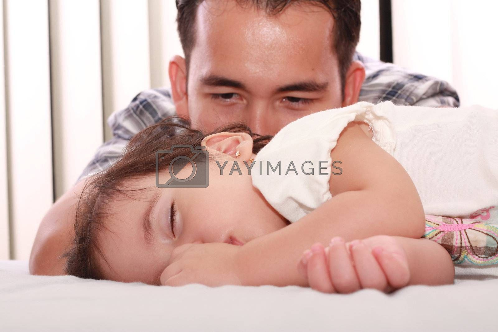 Royalty free image of Father watch his beautiful baby while she sleeps by dacasdo