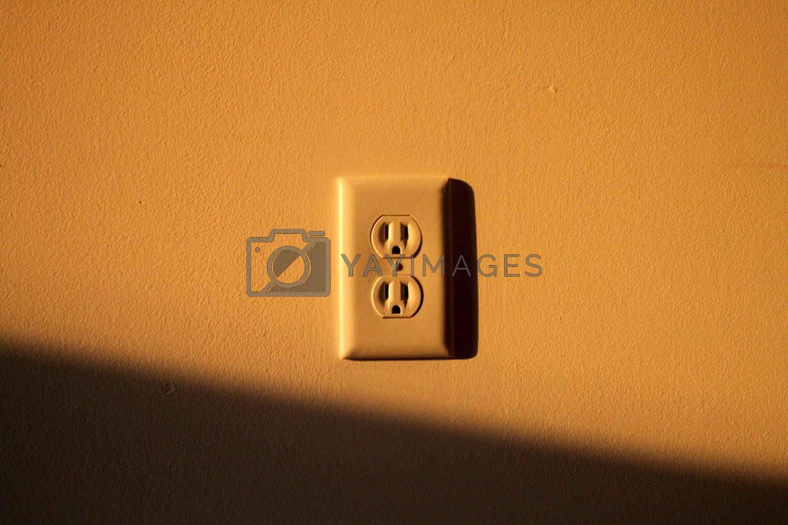 Abstract view of a wall socket with the late sun splashing