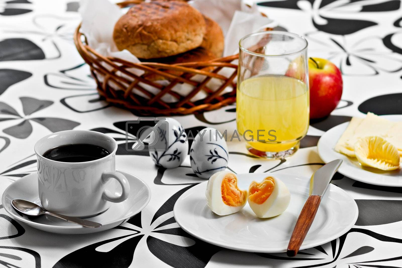 Breakfast with heart shaped egg, coffee, orange juice, bread, butter, cheese and an apple