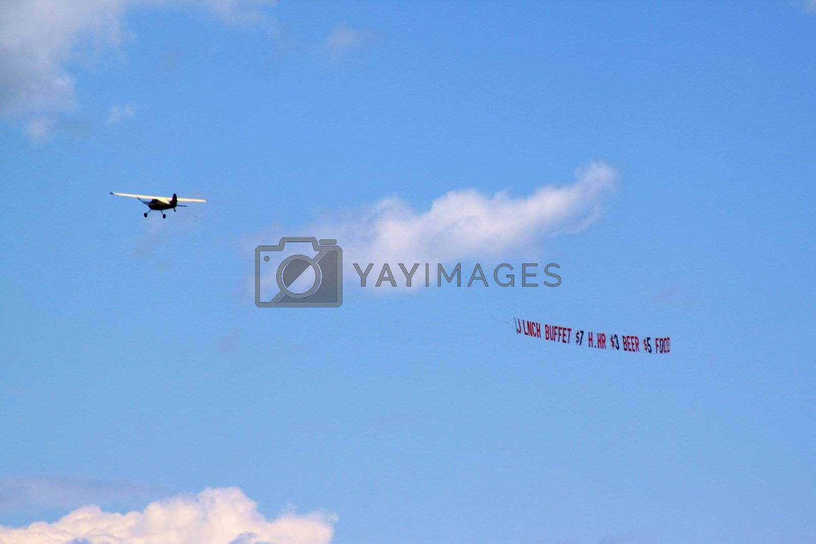 Plane dragging publicity banner through the coastline sky