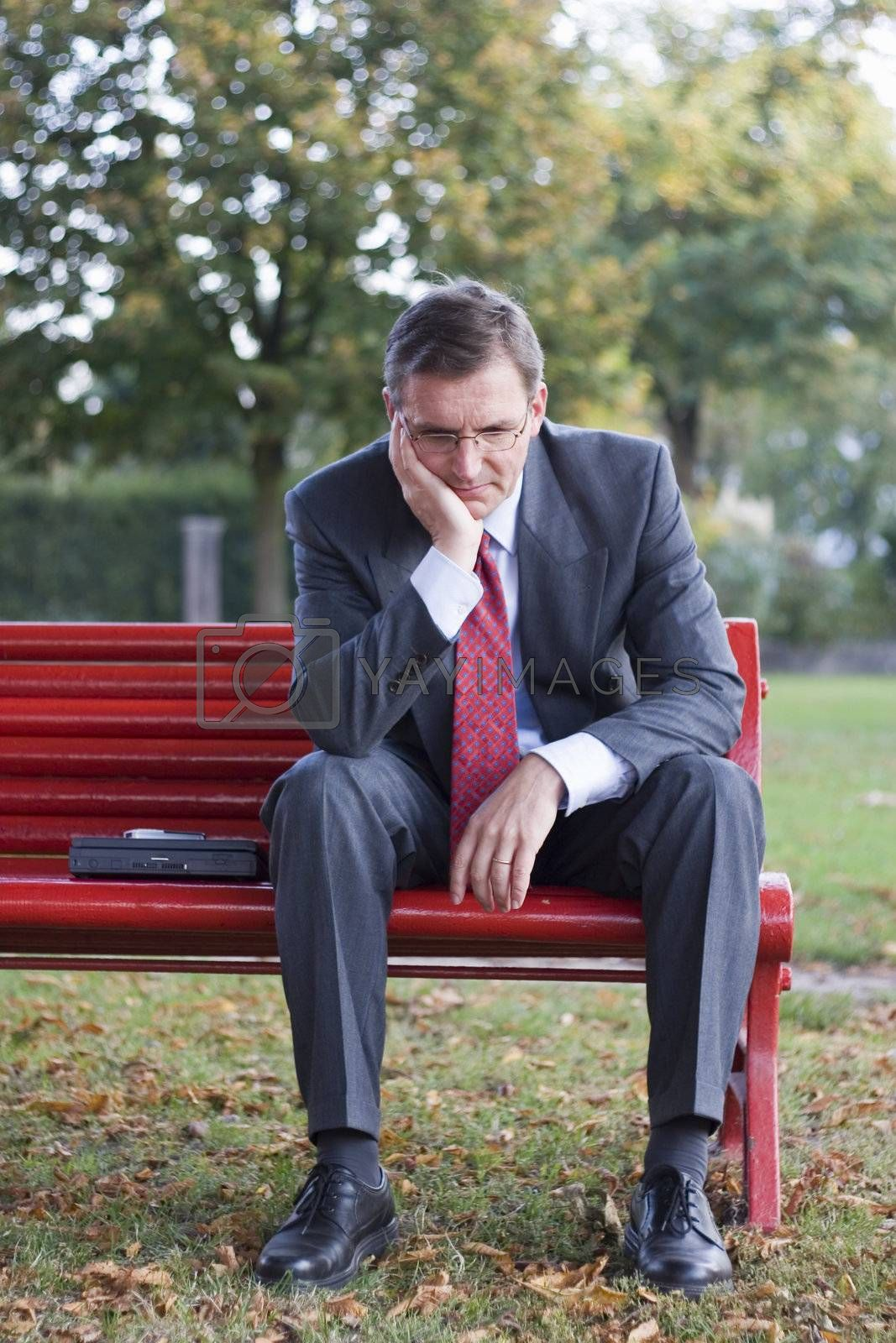 Worried businessman sitting on a red park bench
