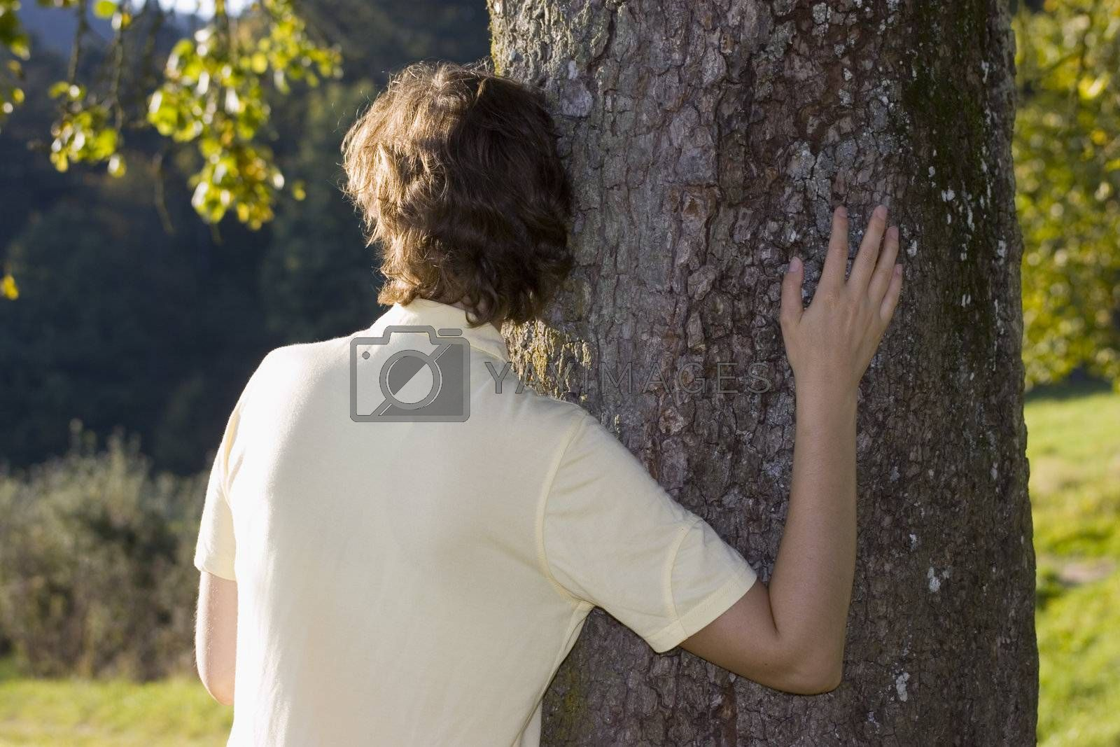 Woman leaning embracing at tree