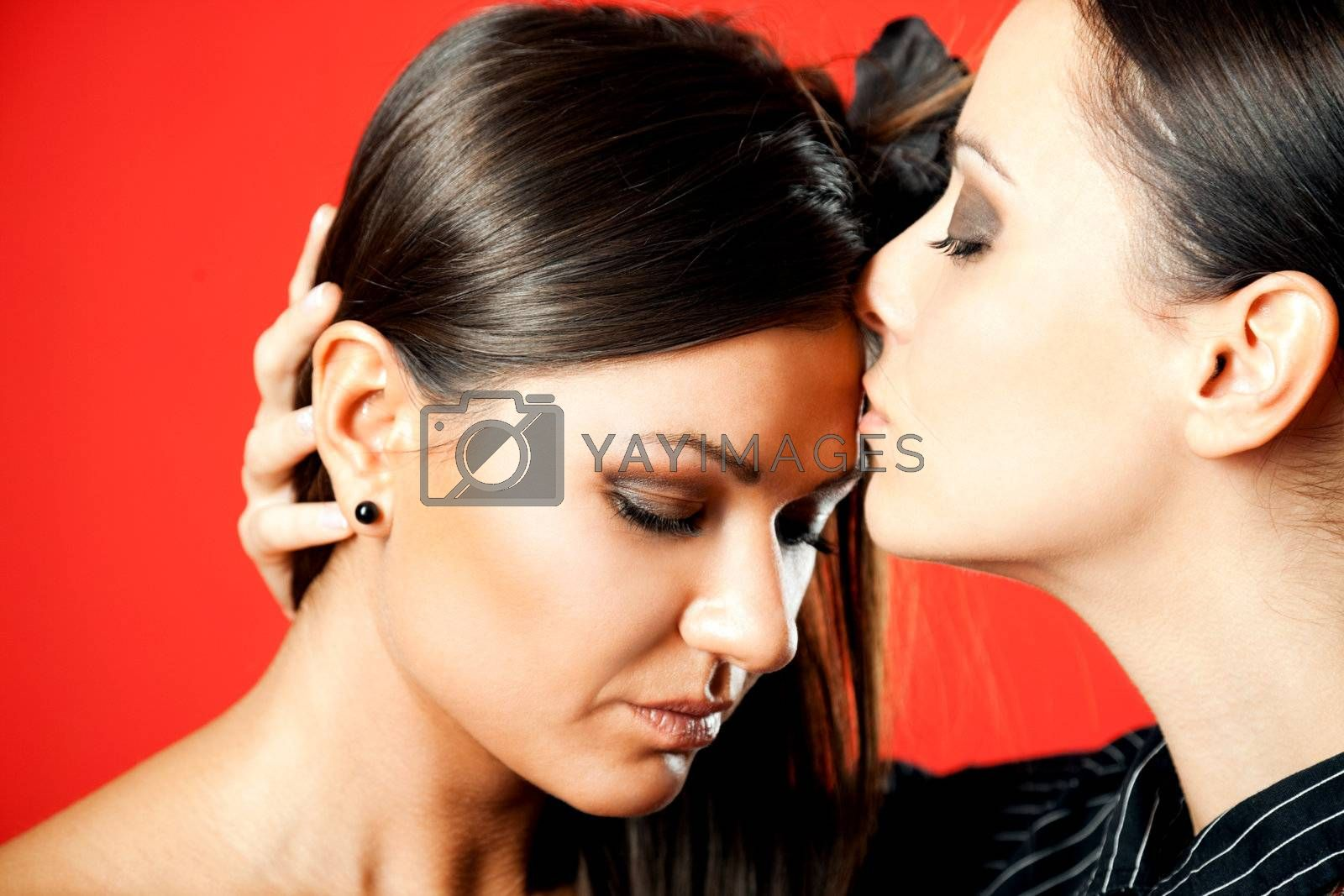 two beautiful females, one kissing the forehead of the other