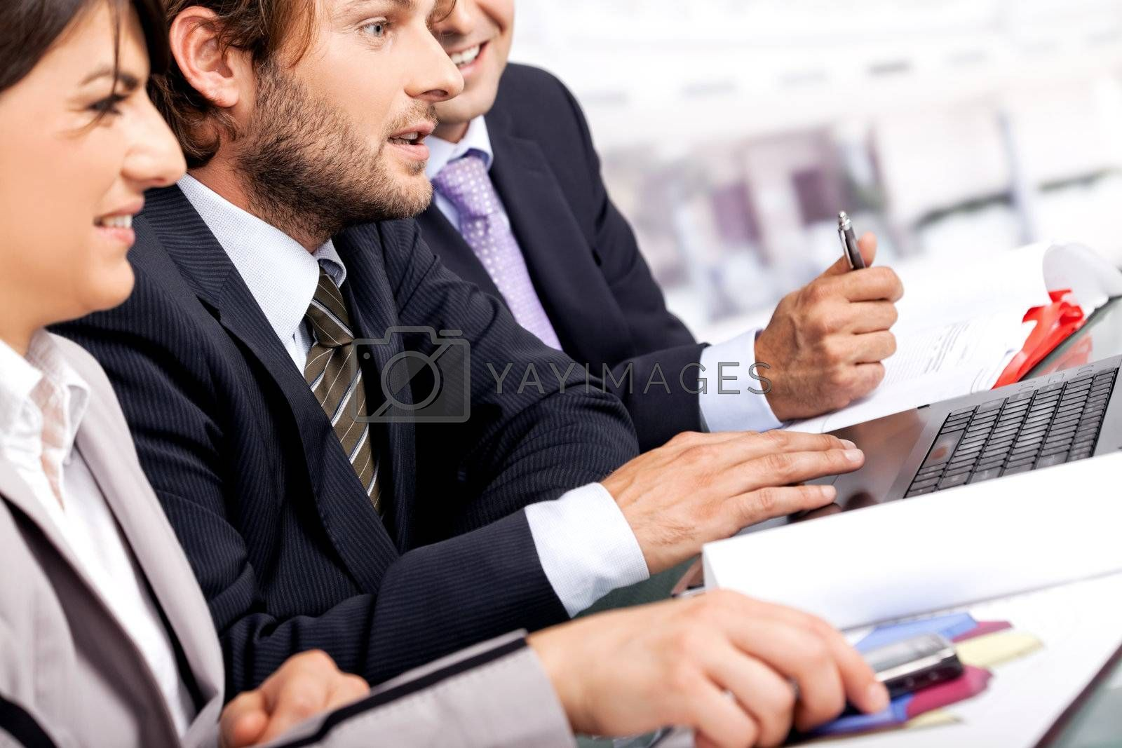 Successful team of three partners working behind laptop