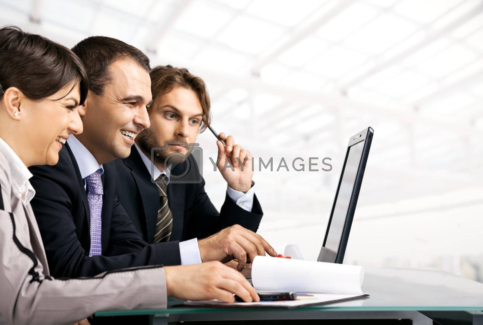 Team of three businesspeople sitting behind laptop, looking at the laptop, copyspace