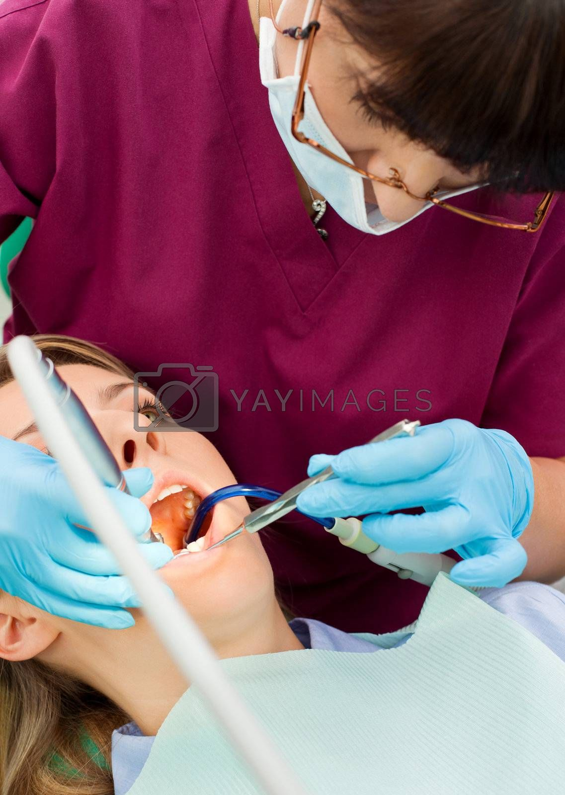 Female dentist with gloves and protective mask working on patient