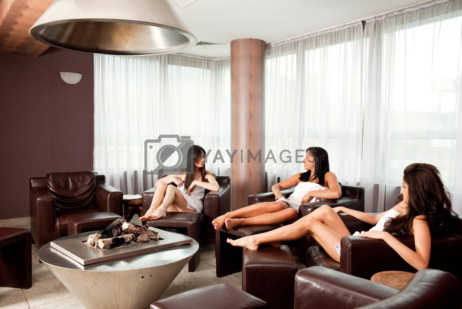Three young females talking  sitting in relax room at spa center