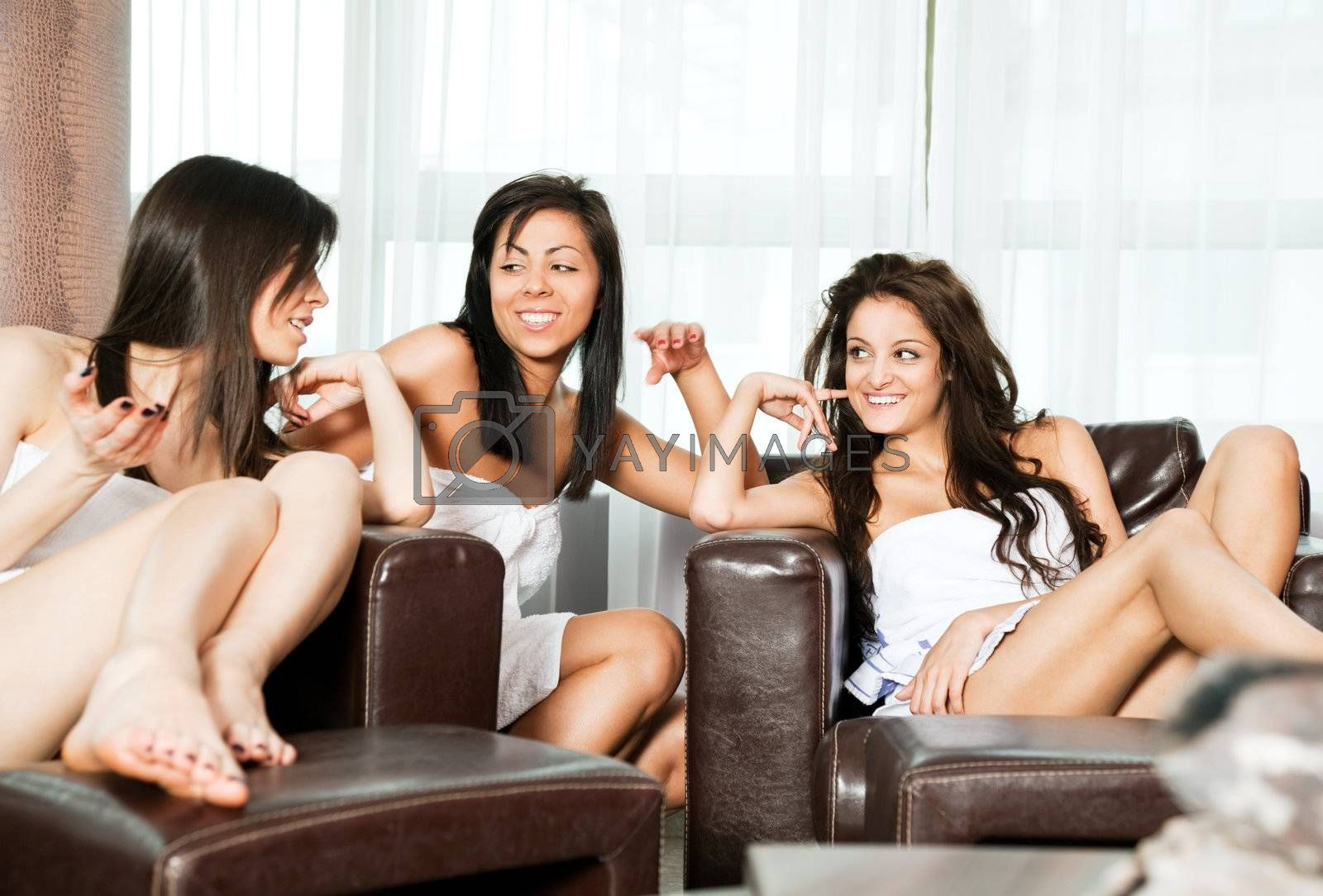 Three young beautiful women talking and relaxing in spa center lobby