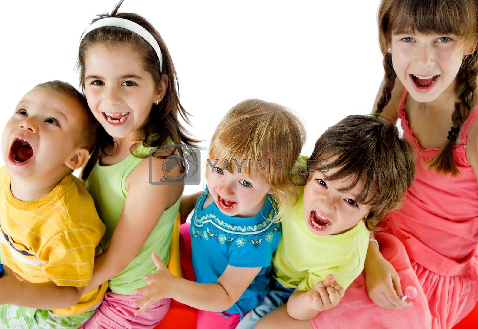 Group of five happy kids sitting, smiling and screaming looking up at camera