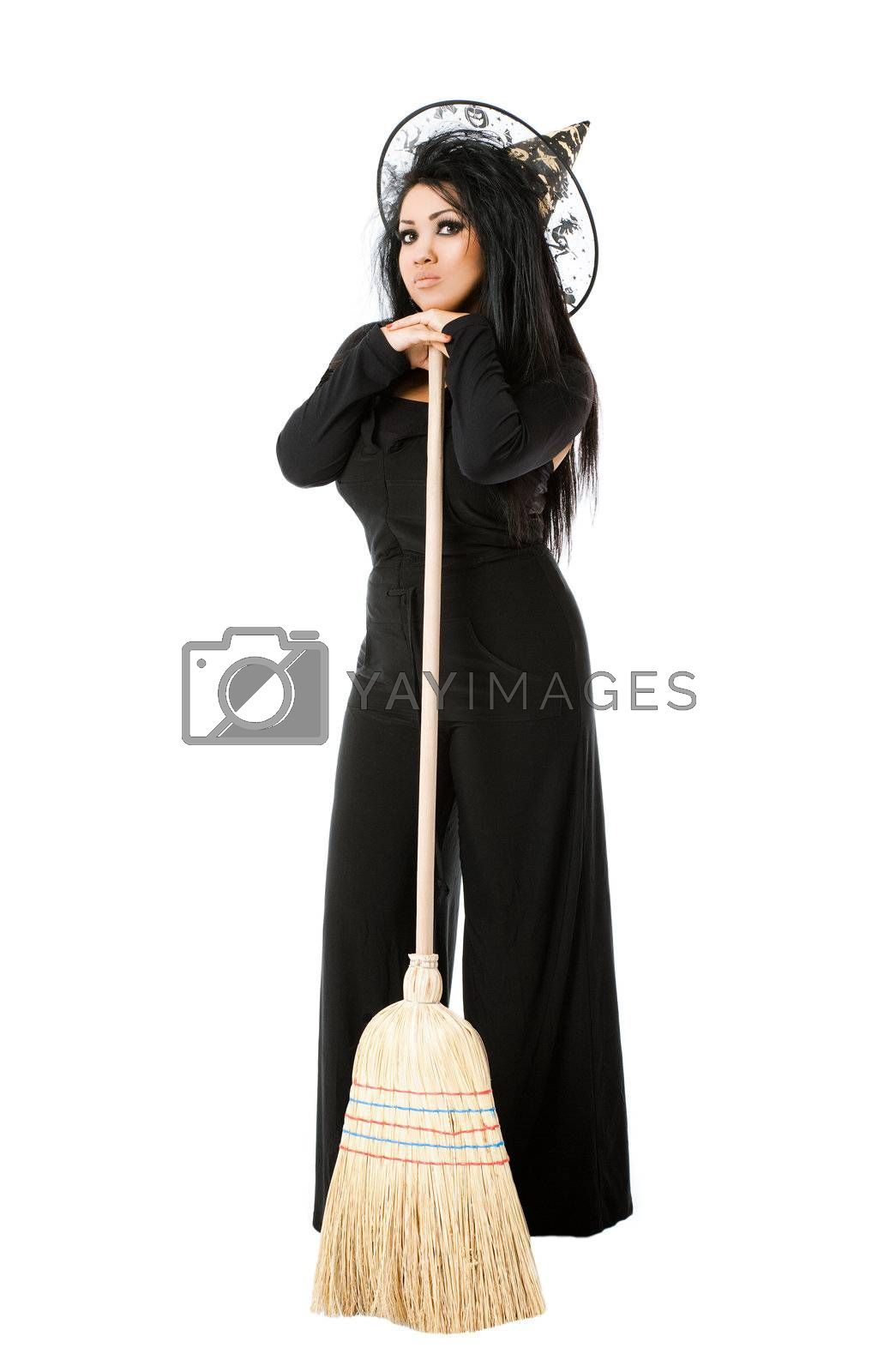 Young female with witch costume standing on white background, leaning on broom