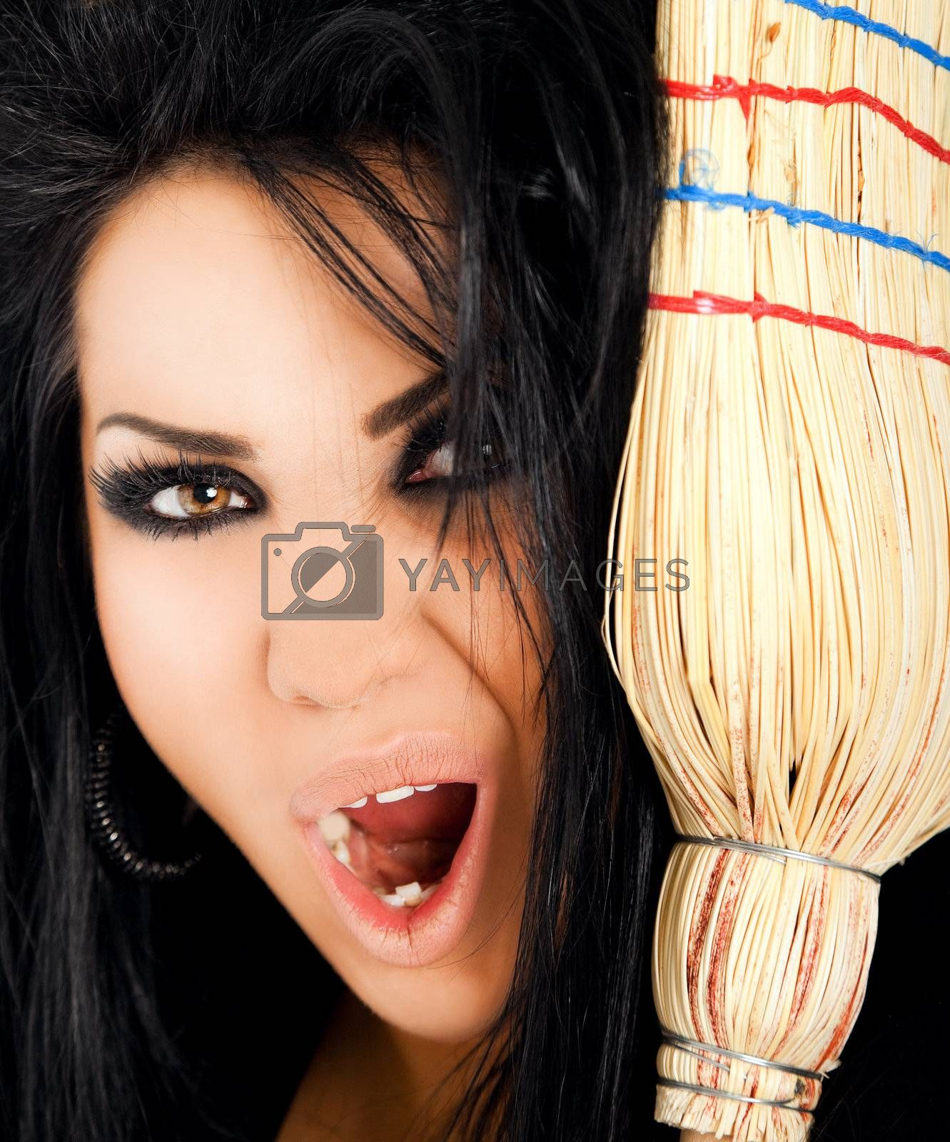 Close-up of female witch looking scary and screaming at camera behind broom