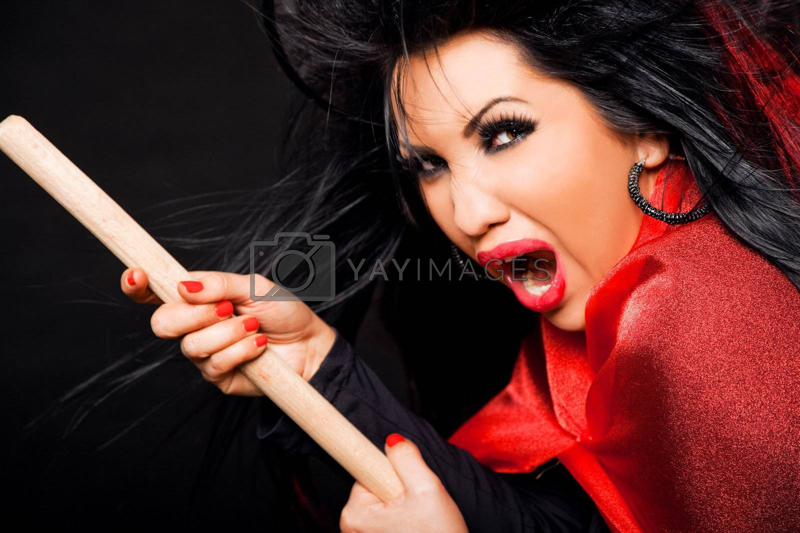 femalewitch with broomstick, looking scary and screaming
