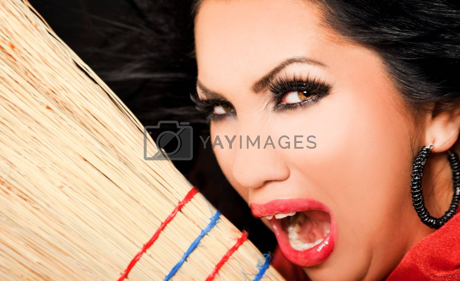 Close-up of female face looking evul at camera, holding a broom screaming