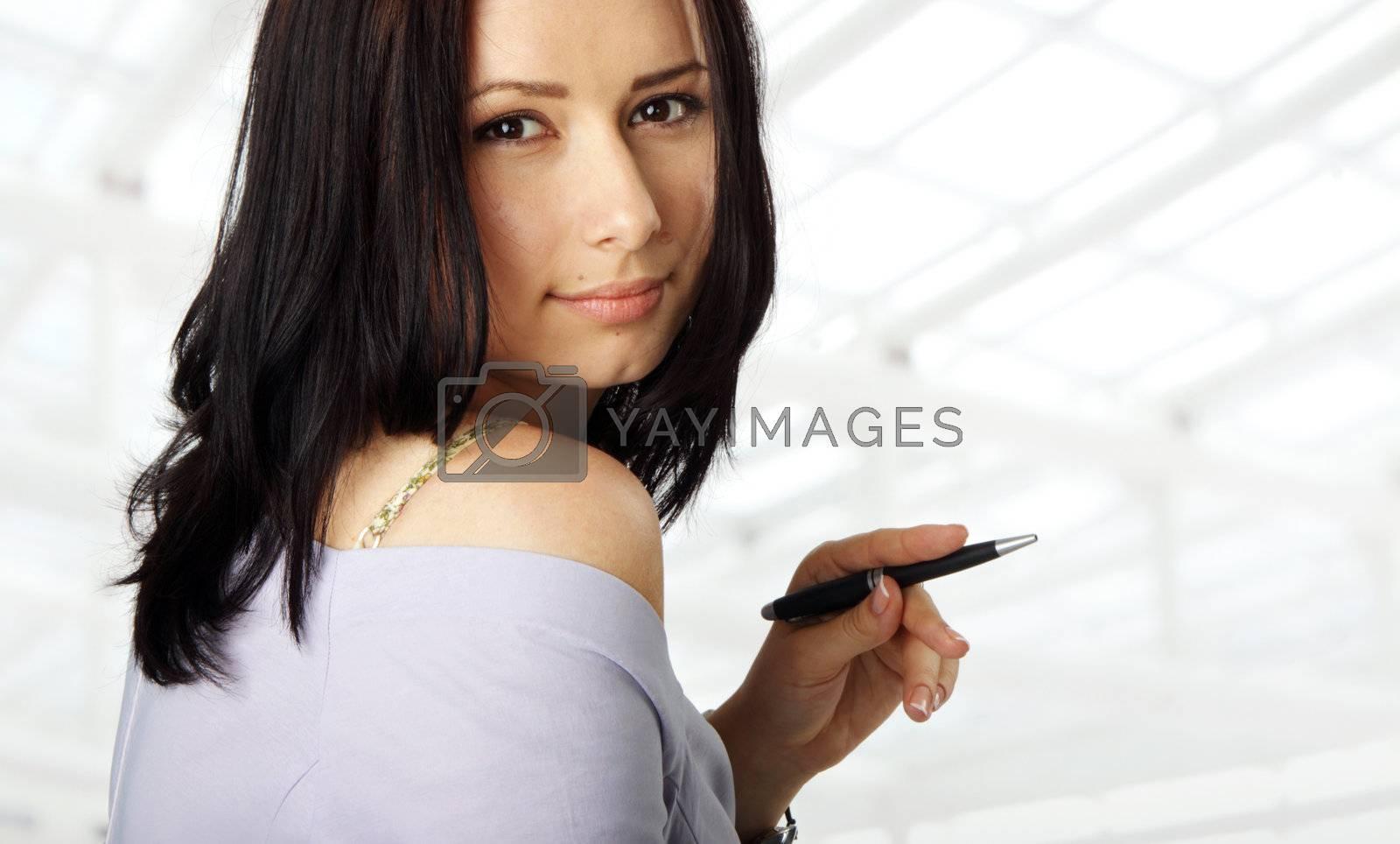 portrait of a beautiful female, holding a pen