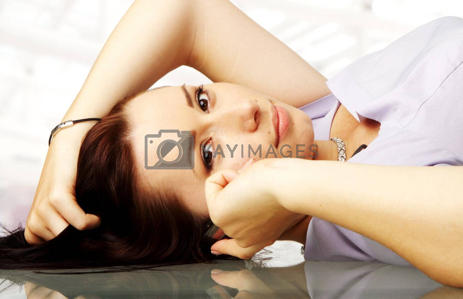 close-up of a female lying on a desk while talking on her cellphone