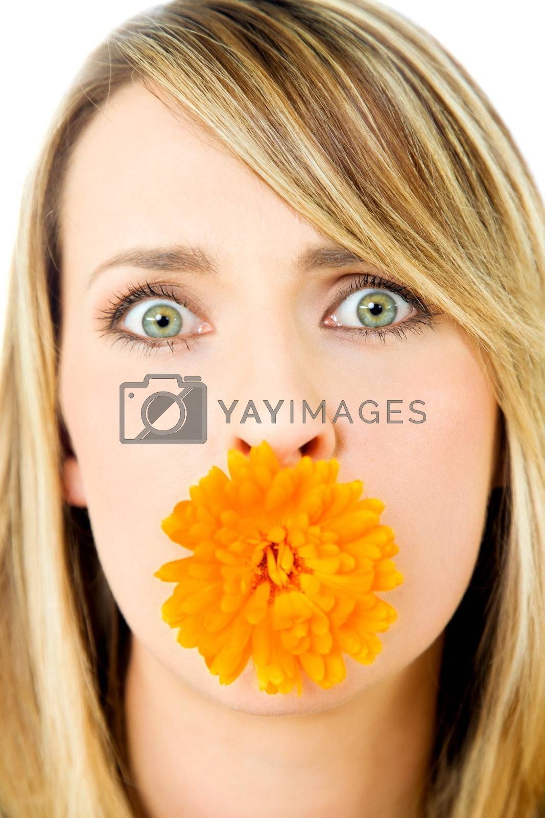 Close-up of beautiful blond female with marigold flower in mouth, staring at camera