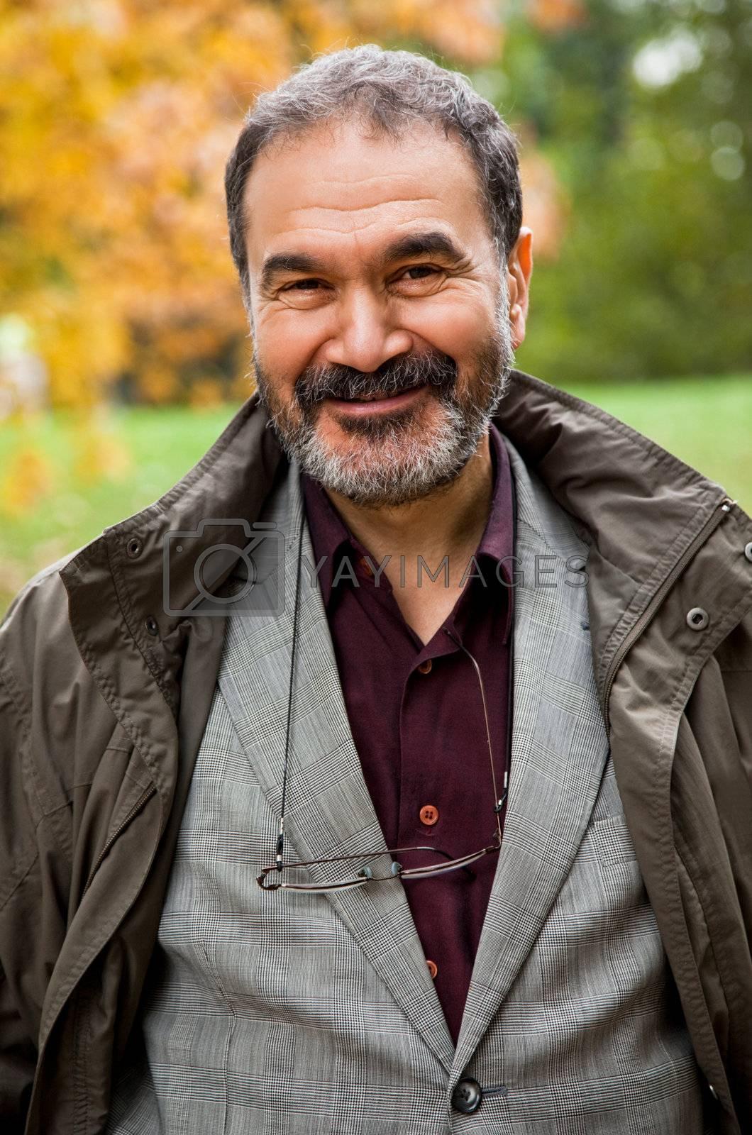 Portrait of happy adult man smiling in autumn park
