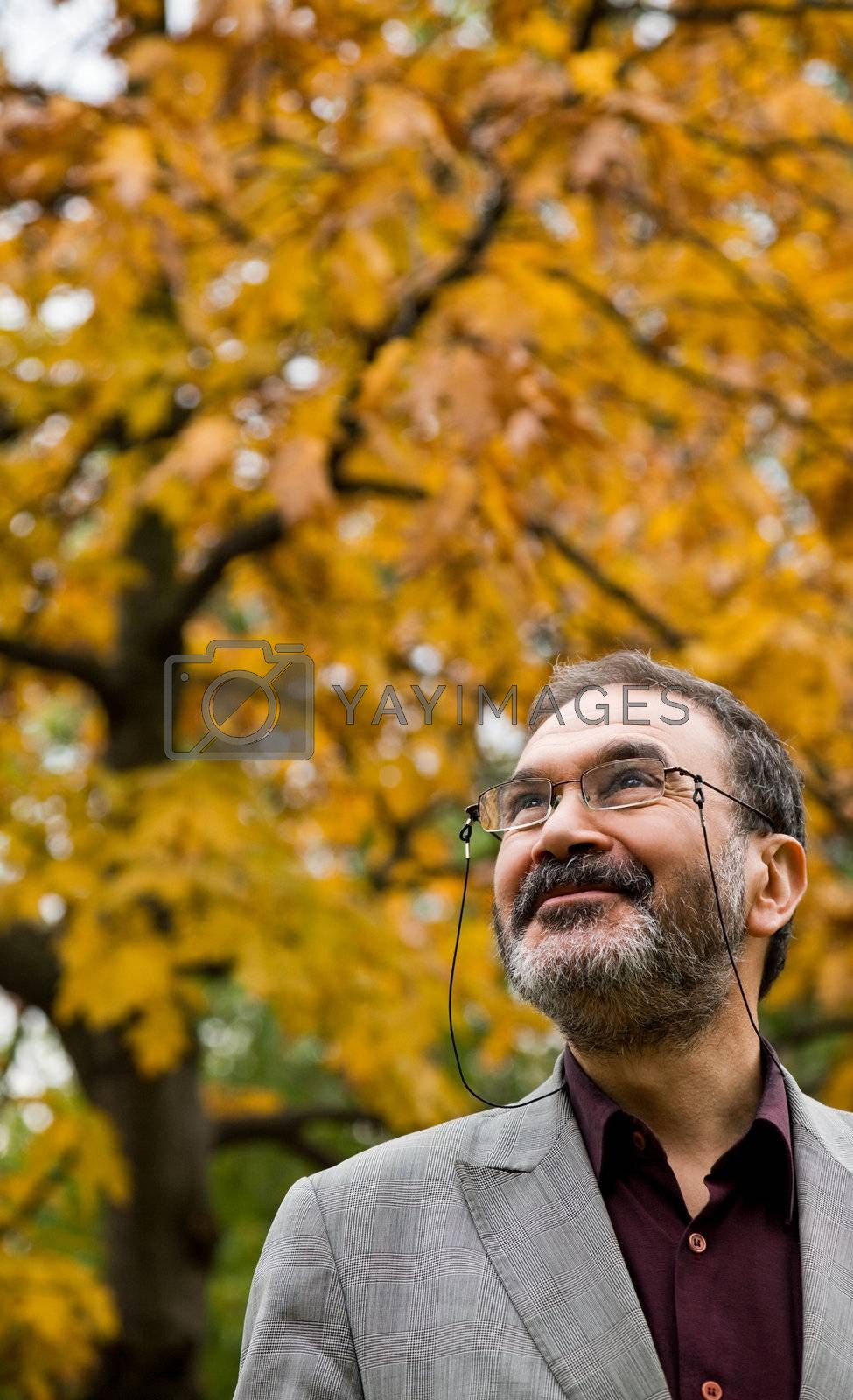 Portrait of happy adult man in autumn park, smiling and looking up