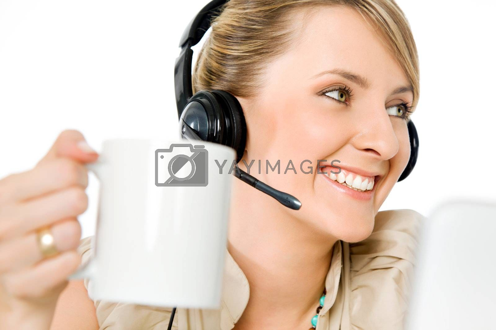 Portrait of beautiful smiling call center woman holding cup, looking left