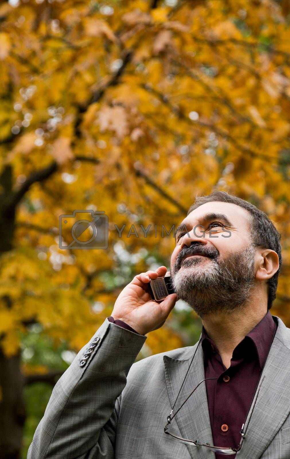 Portrait of positive adult man talking on mobile phone, autumn day, looking up