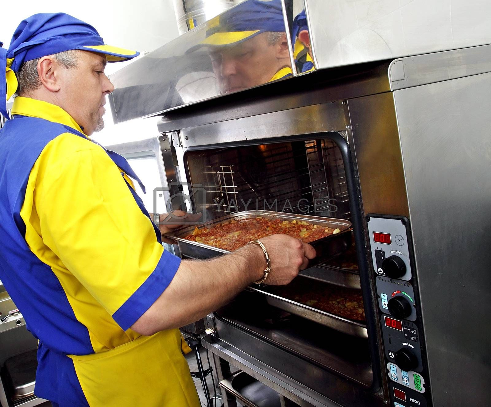 a cook inserts a dish in the oven