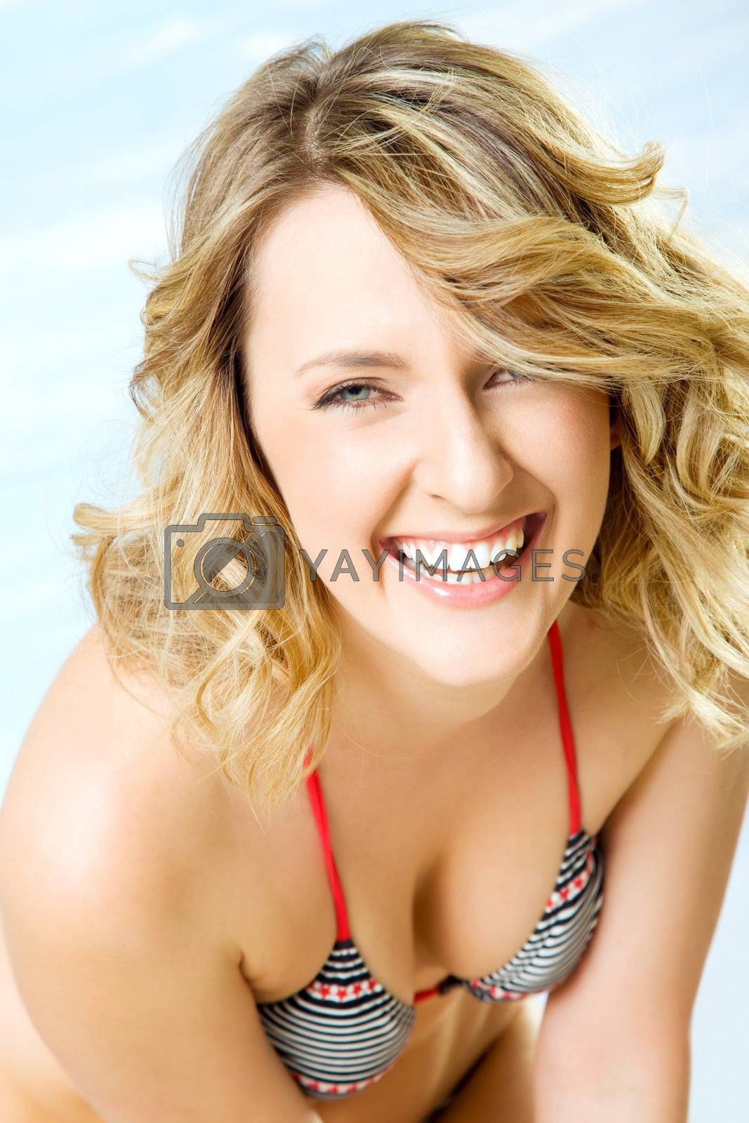 Close-up of happy beautiful blond woman in swimsuit, smiling at camera