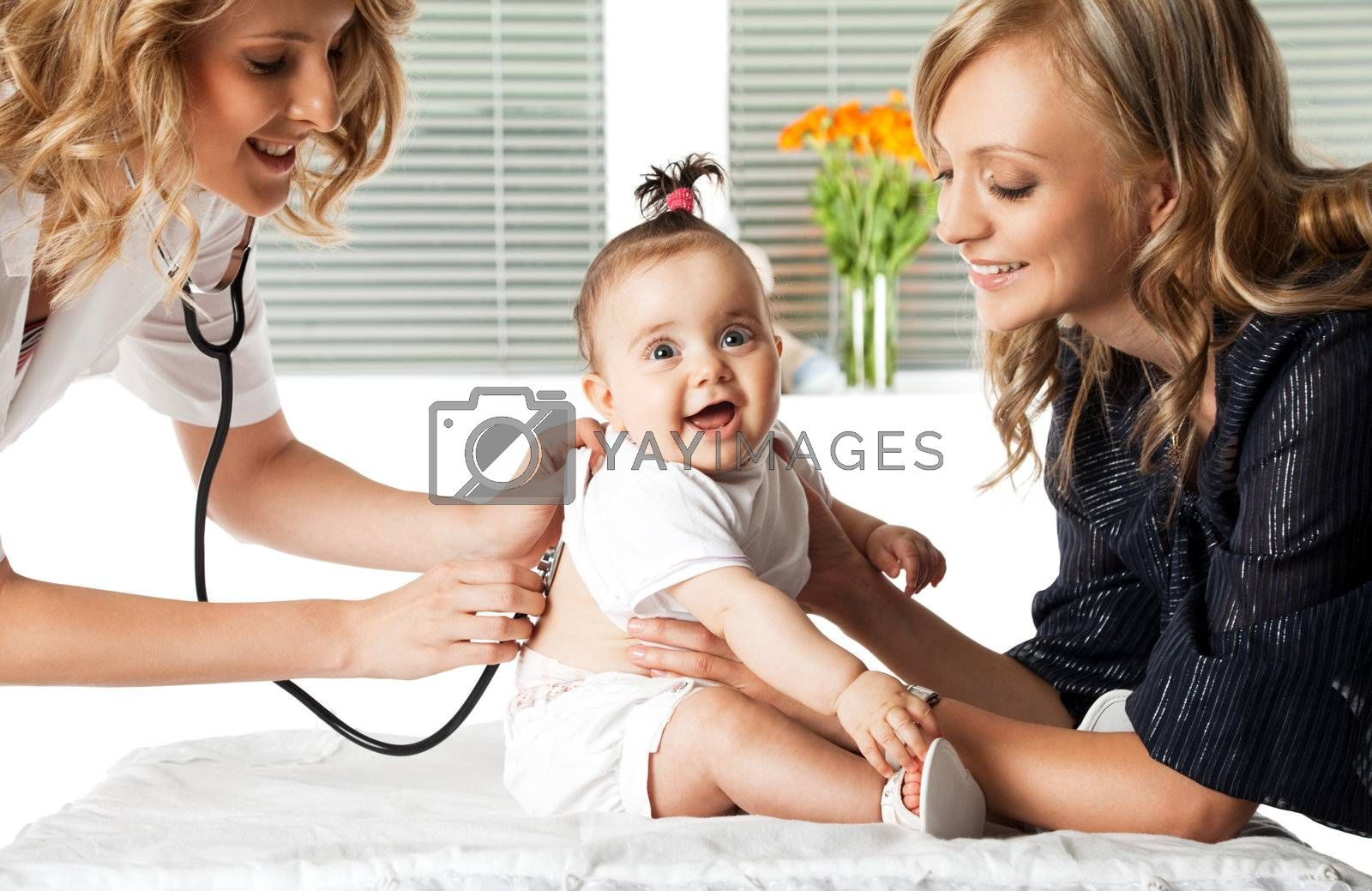 Female doctor examining little smiling baby girl held by her mother