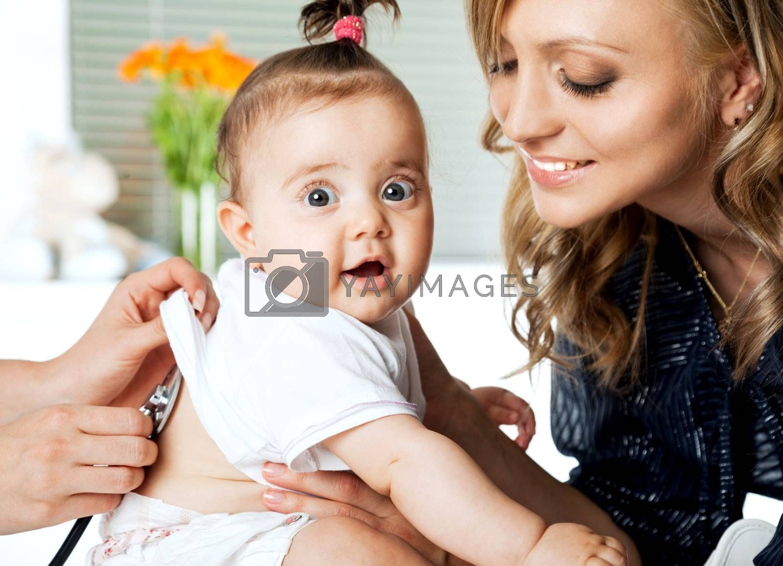 Sweet little baby girl in hospital being examinated and held by mother