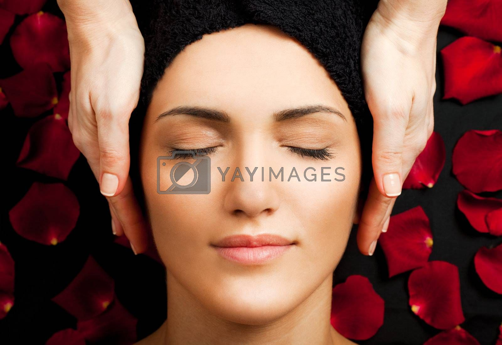 Beautiful young woman receiving face massage at spa