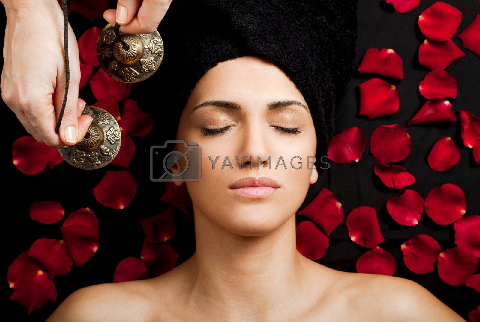 Close-up of beautiful female receiving energy sound massage at spa