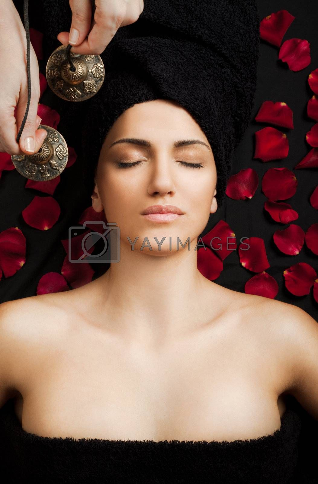 Beautiful female receiving energy sound massage in spa, eyes closed