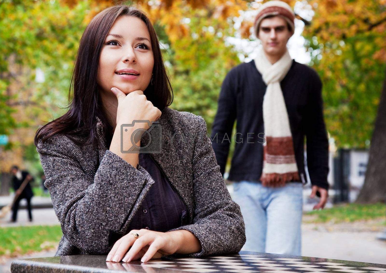 Young woman sitting in park, male coming from behind